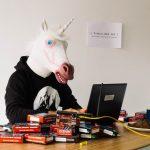 Un homme avec une tête de licorne devant un ordinateur et un tas de briques internet